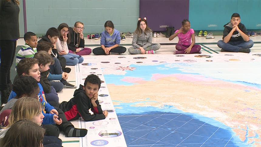 Kids sit cross legged around a giant map on the floor.