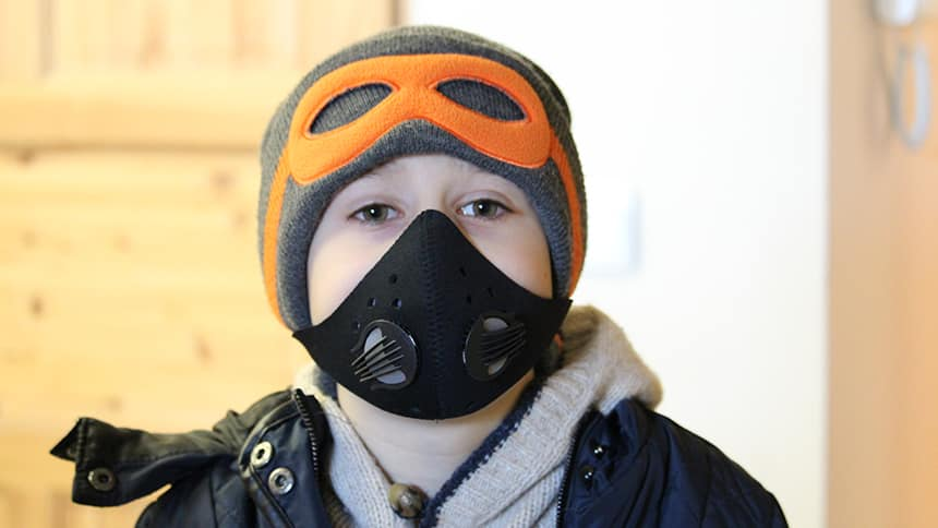 Boy in winter clothes wears black mask over his mouth and nose.