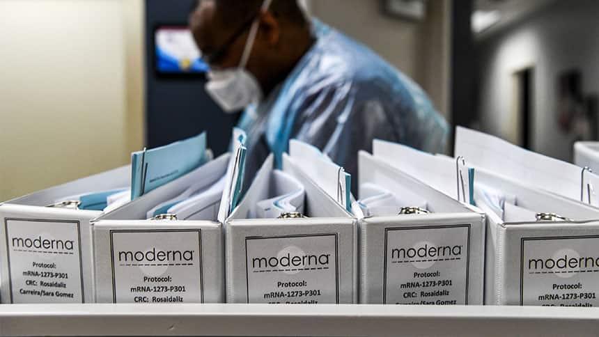 Man works behind row of binders labelled Moderna.
