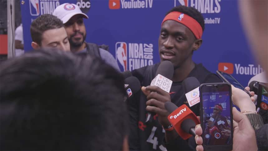 A basketball player talks in a microphone