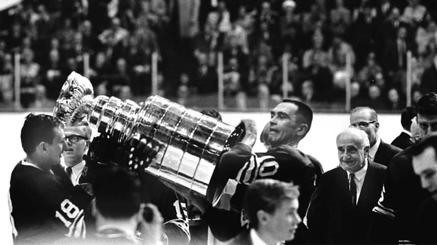 A black and white image of hockey players hoisting the Stanley Cup