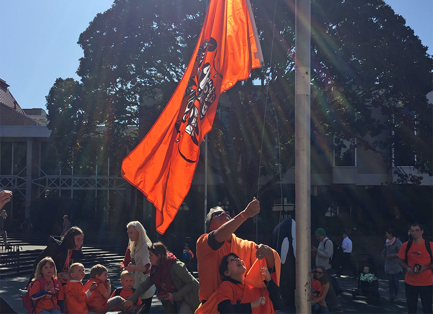 Haley and her dad raise a massive orange flag triumphantly up a flagpole.