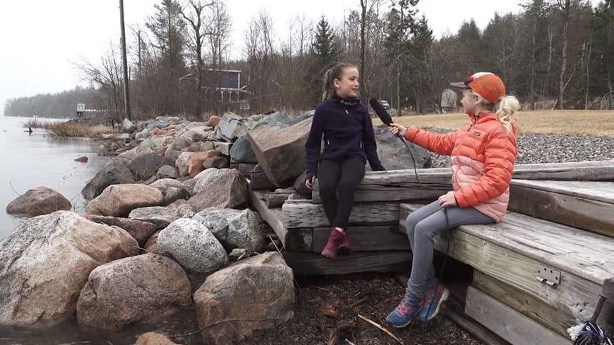 Olivia Chamberlain and Kaiya Hemmings sit on backyard steps dangling legs over water.