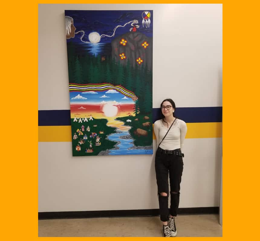 A teen stands beside a large painting hanging on a wall.