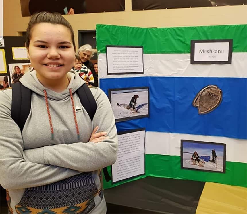 A teen stands beside a school project.