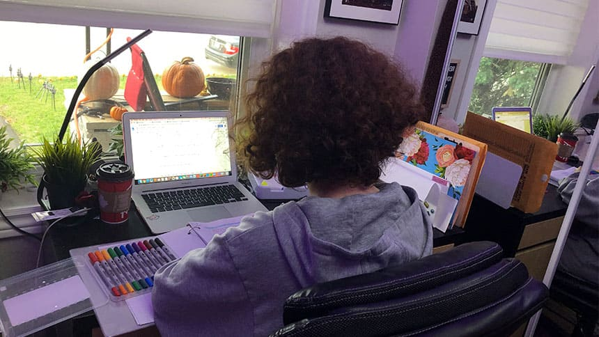 A teen sitting at a desk with a computer