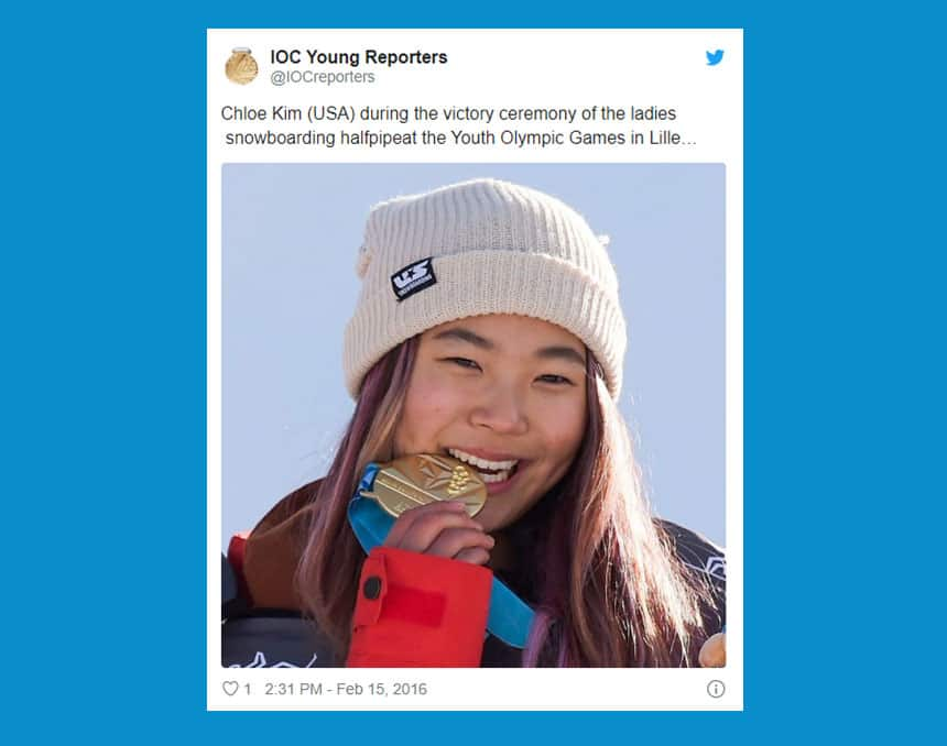 IOC Young Reporters Tweet (@IOCreporters) post text reads: Chloe Kim (USA) during the victory ceremony of the ladies snowboarding halfpipe at the Youth Olympic Games in Lillehammer. Photo is of Chloe biting her gold medal.