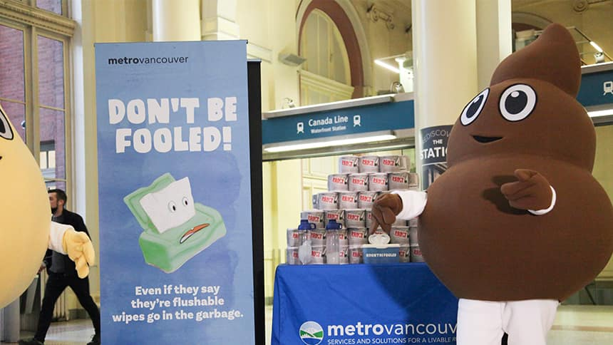 A person in a poo mascot outfit stands at a booth about flushable products.