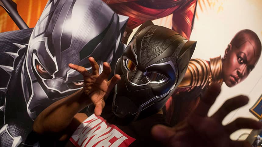 Children dressed up in costume in front of a poster of Marvel Studio's Black Panther movie