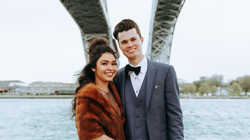 A couple dressed up in fancy clothes pose under a bridge.
