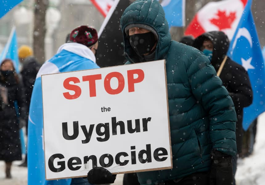Man holds sign that says Stop the Uyghur Genocide