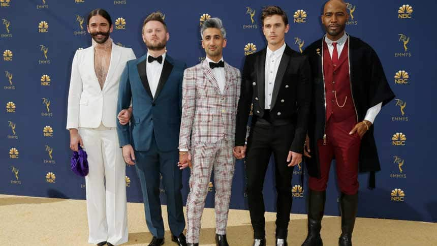 Five men pose for cameras on a gold carpet with a blue Emmys backdrop.
