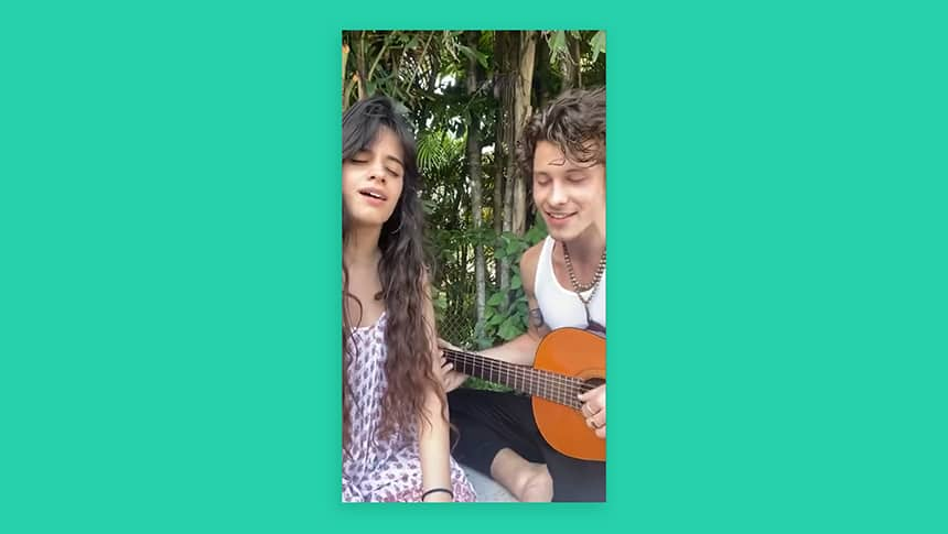Singers Camila Cabello and Shawn Mendes sit beside each other singing.