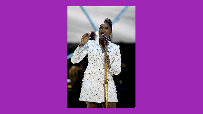 Jennifer Hudson, dressed in all white sings on a stage.