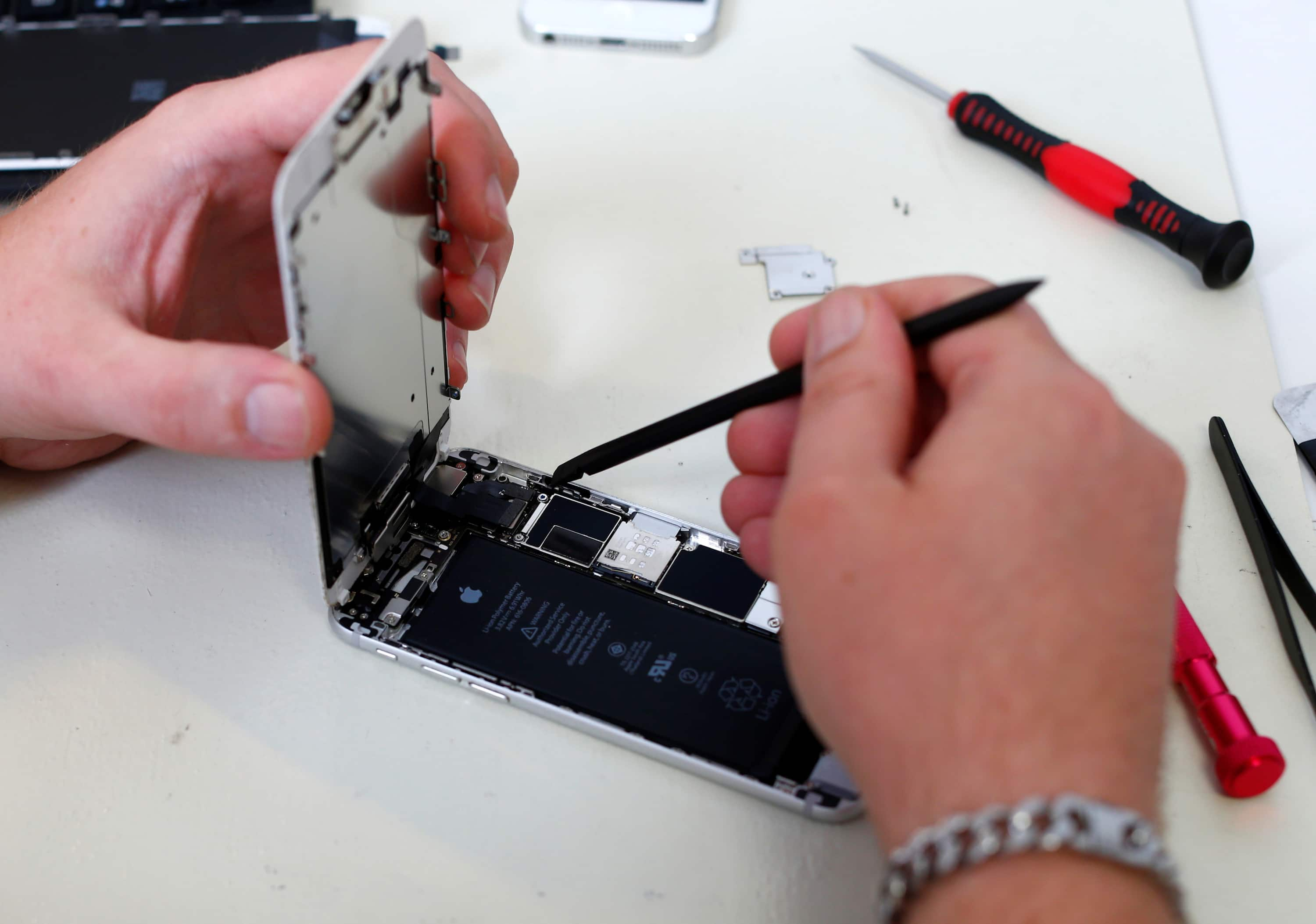 Someone opening up an iPhone with tools