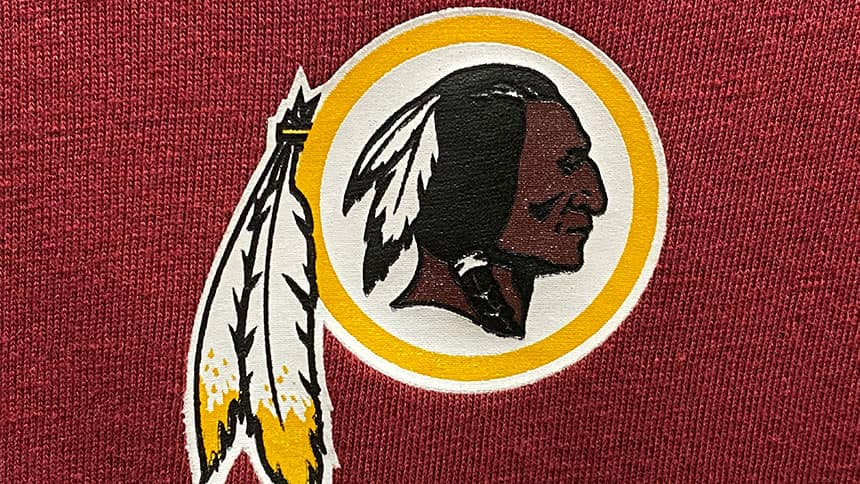 Redskins logo show Indigenous man in profile with traditional braid and feathers.
