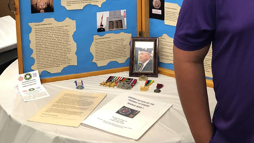 War medals and a picture of a veteran beside a poster on a table.