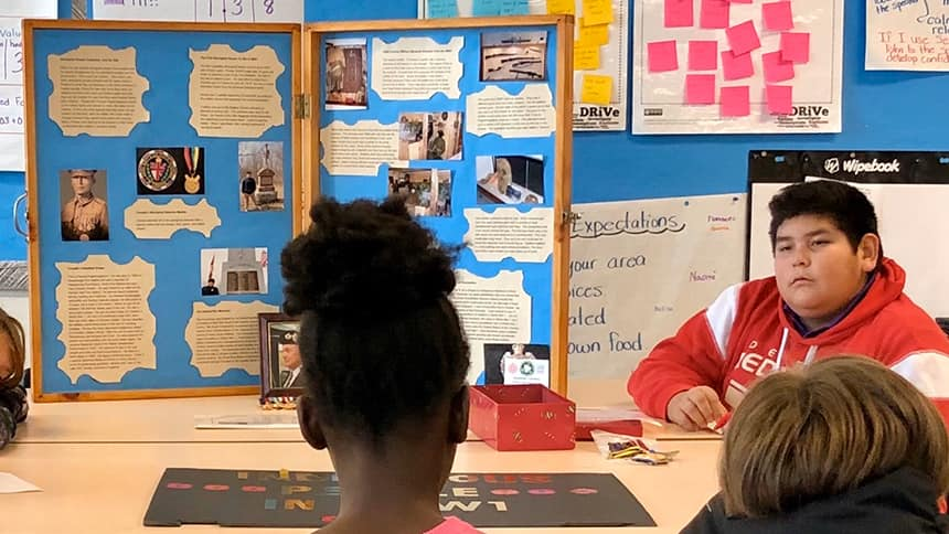 A teen sits at a table beside a poster with war memorabilia, talking to kids.