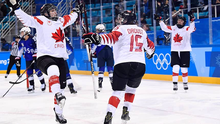 Two female hockey players celebrate on the ice