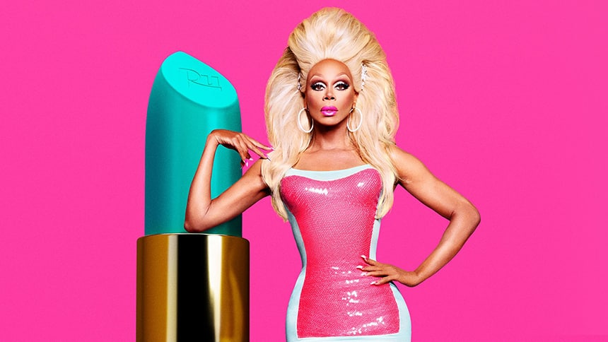 Rupaul looking very tall eyeing down the camera with a massive blonde wig standing next to a giant lipstick prop