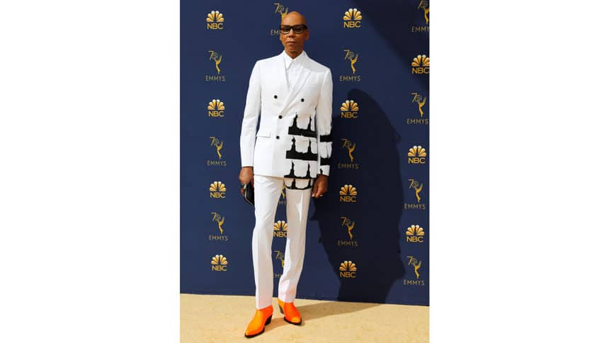 Man stands on gold carpet with Emmys backdrop.
