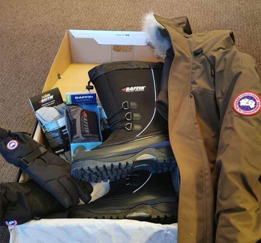 An open box with boots, a coat, gloves and other winter clothes