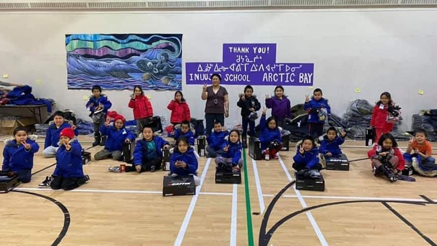 A group of kids in a gym wearing parkas