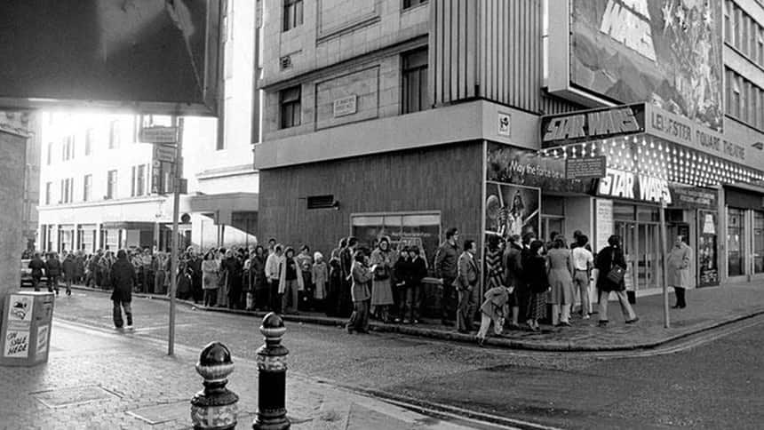 Black and white image of a line of people in front of the cinema.