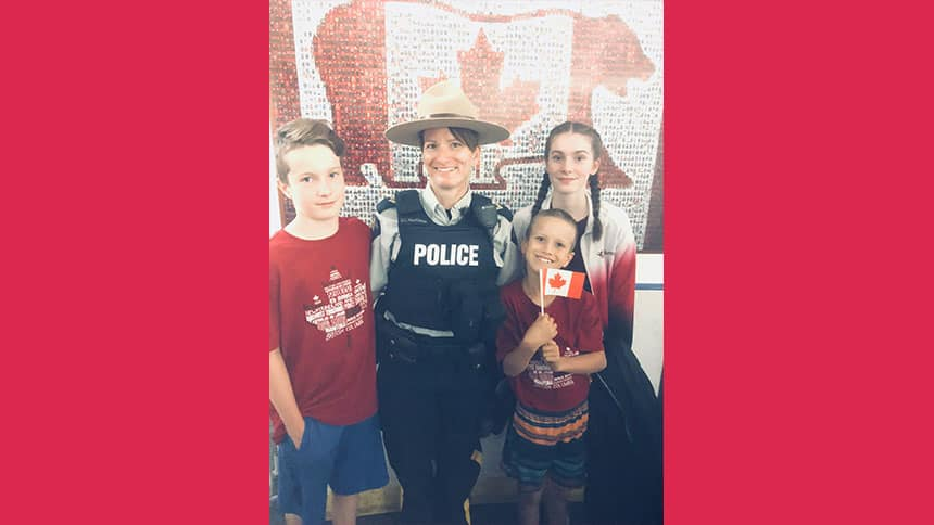 Sally Mackinnon in RCMP uniform surrounded by her three kids.