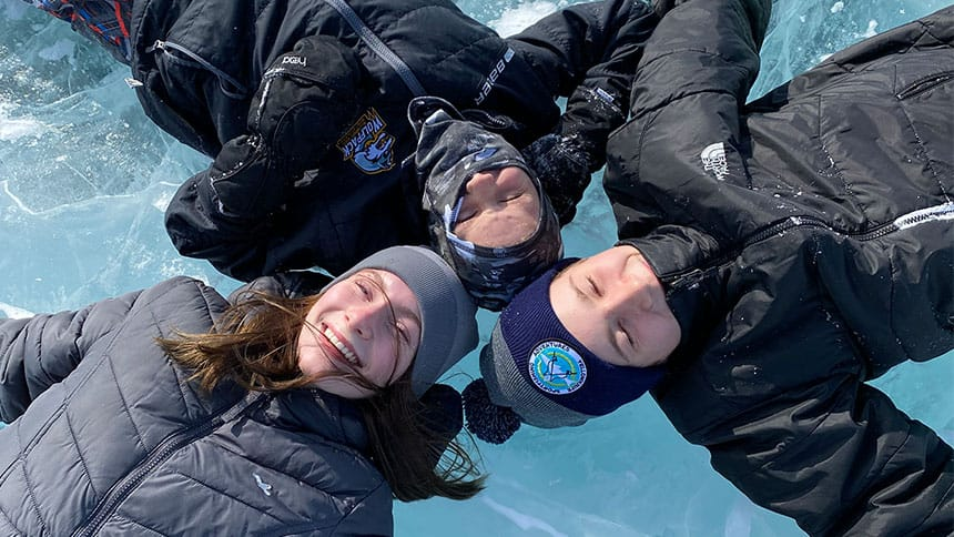 Three Mackinnon kids lie with their heads together on a frozen lake.