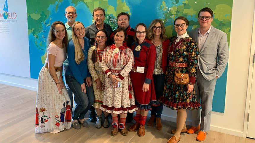 Group of people, half of whom are wearing traditional Sami clothing.
