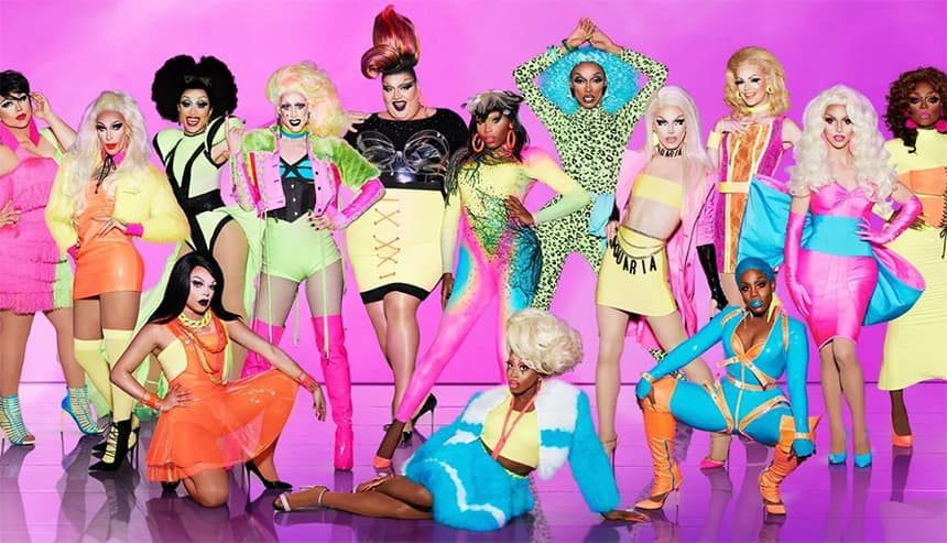 A large group of colourful drag queens in elaborate outfits and wigs pose for the camera in a line