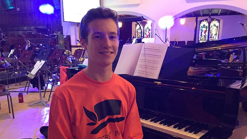 A teenager sits by a piano in a church.