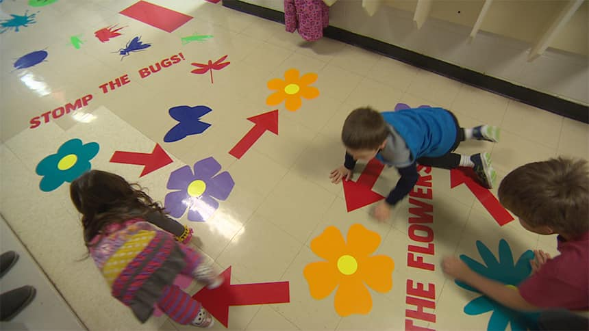 Kids crawl along flowers painted on the floor