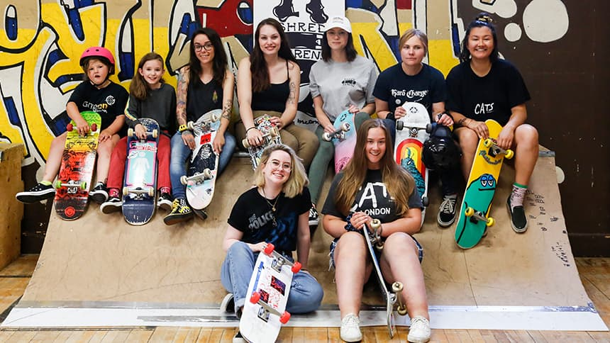 A group of girls, teens and women with skateboards