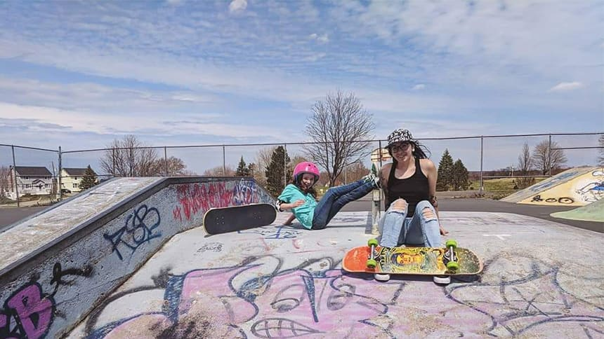 A girl and a woman hang out in a skate park.