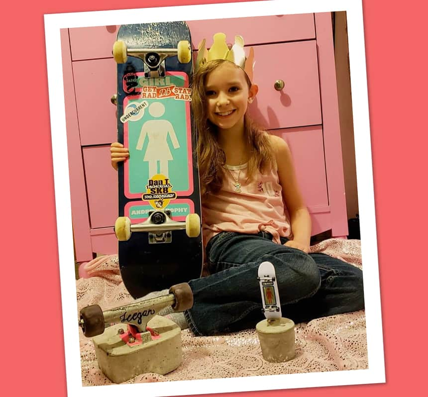 A girl poses with a skateboard and a home-made trophy.