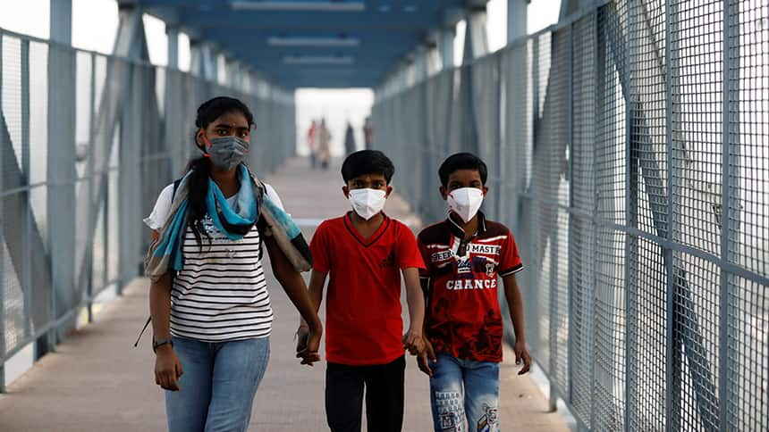 A woman and 2 children walk across a bridge in a smoggy city wearing masks.