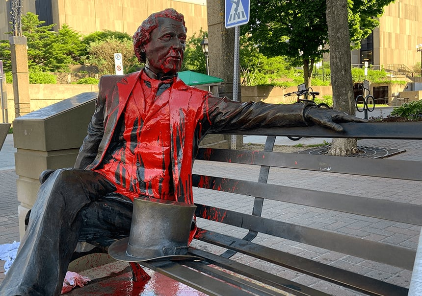 A picture of Sir John A. Macdonald's bronze statue sititng on a park bench covered in red paint