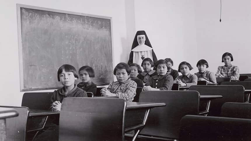 Black and white photo of a group of students sitting in a residential school classroom
