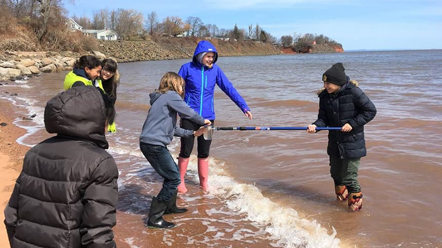 Bowles with other children at the water showing them how to test it