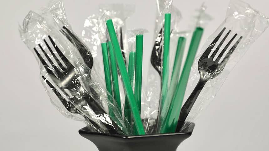 Plastic forks and straws in a cup