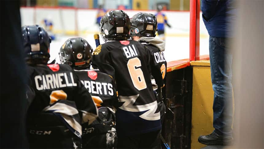 Yamen Bai and a group of young boys stand at the edge of a rink during a game last week.