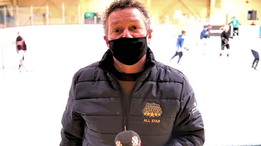 Hockey dad Michael Doyle being interviewed in front of an ongoing hockey game.