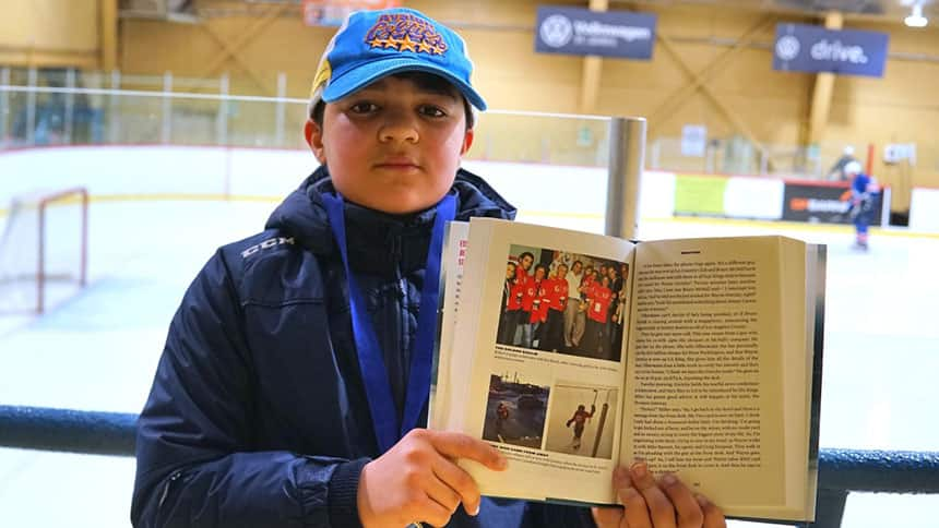Yamen Bai holds a book written by James Duthie, a broadcaster for The Sports Network (TSN) who included a chapter in his book about Yamen's journey into hockey.