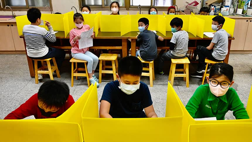 Students with masks on sit in desks separated by plastic dividers.