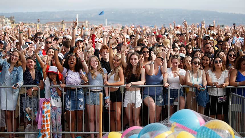 A huge crowd of fans with the beach in the background.