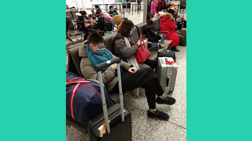 A teen and a woman sit in an airport with masks on