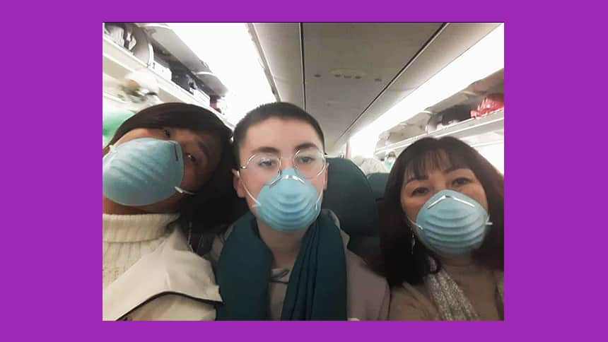 Three people on a plane wearing masks