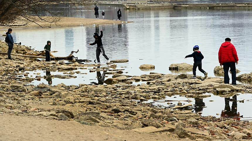 Kids play on rocks on the edge of a lake
